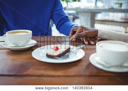 Mid section of couple holding hands while having coffee in cafeteria