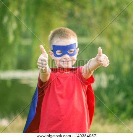 Kid in super hero costume showing thumbs up. Selective focus on thumbs up. The winner and success concept.