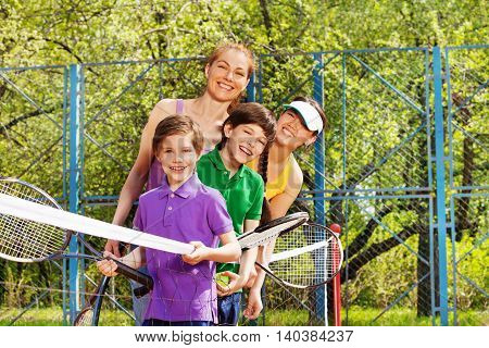 Active family, mother and three kids, having fun playing tennis, standing one by one close to the net