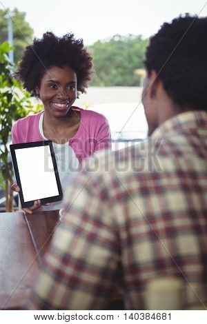 Smiling woman showing digital tablet to man in cafe