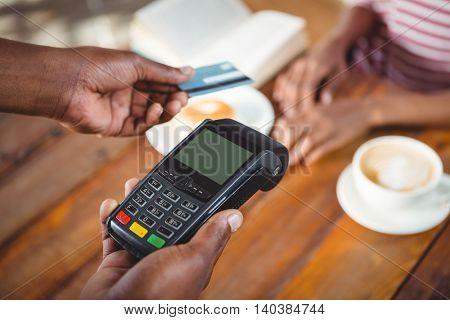 Waiter holding credit card machine in cafe