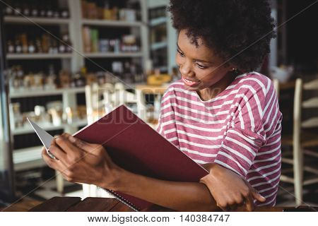 Smiling woman sitting in cafe reading menu