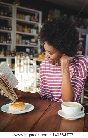 Smiling woman sitting in cafe reading a book