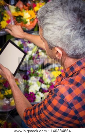 Close-up of male florist using digital tablet at his flower shop