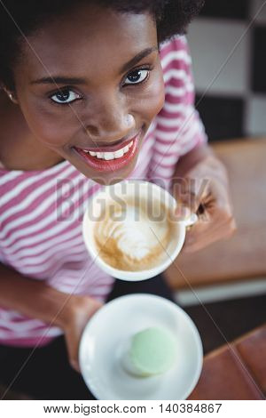 Portrait of smiling woman drinking cup of coffee in cafe