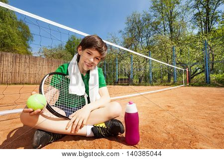 Kid boy having rest after playing tennis, sitting on the clay court near the tennis net, holding racket and ball