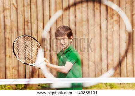 Happy young tennis player, kid boy holding racket and ball, preparing to serve, view through the racket net