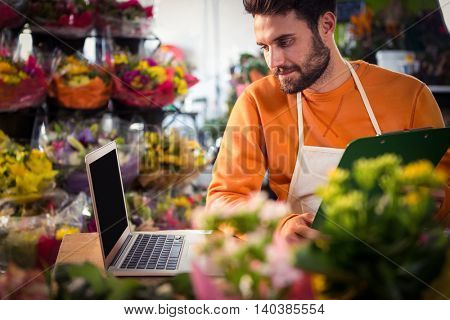 Male florist checking order in laptop at his flower shop