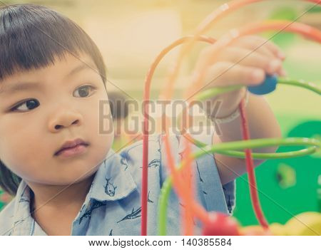 Asian children playing on educational toy. Japanese baby learning to count with colorful toy. Number learning practice in kindergarten class room for children.