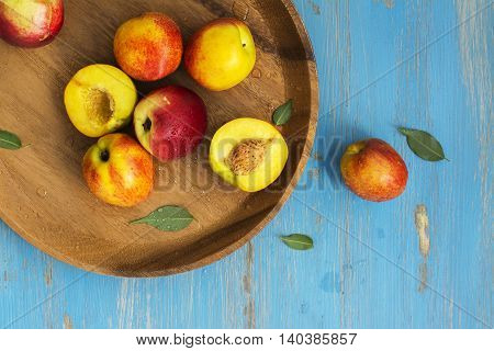 Ripe juicy nectarines over blue wooden table. Top view. Space for text