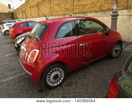 ROME ITALY - CIRCA JULY 2016: red Fiat New 500 car parked in a street of the city centre