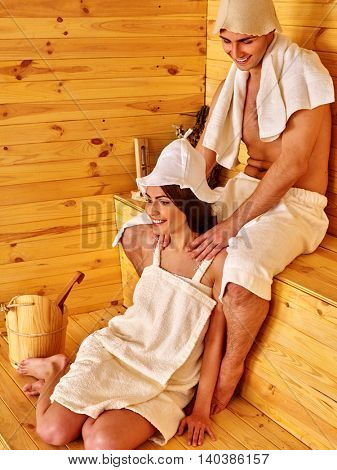 Young couple in sauna hat relaxing at sauna. Two people have rest in sauna.