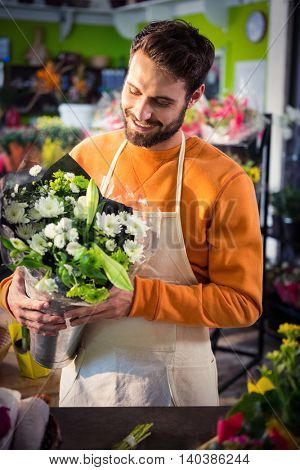 Happy male florist holding flower bouquet at his flower shop
