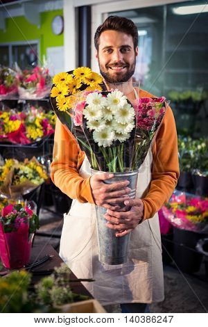 Portrait of male florist holding flower bouquet at his flower shop