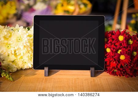 Close-up of digital tablet on table at flower shop