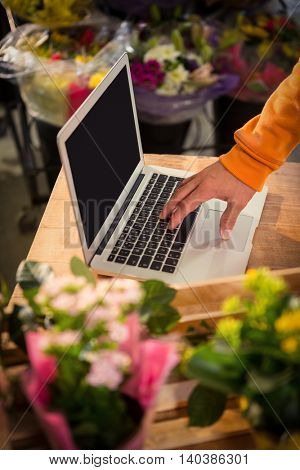Male florist using laptop at his flower shop