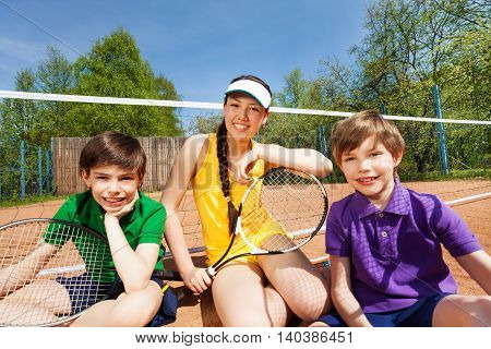 Portrait of tennis team, teenage girl and two kid boys, sitting on the clay court after match