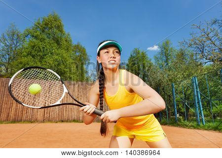 Professional tennis player, determined young girl in action on the clay court in summer