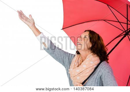 Mature woman holding umbrella while standing against white background
