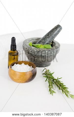 Aromatherapy oil with rosemary and mortar and pestle on white background