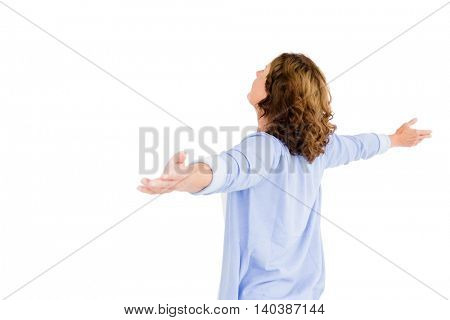 Woman with arms outstretched while praying against white background