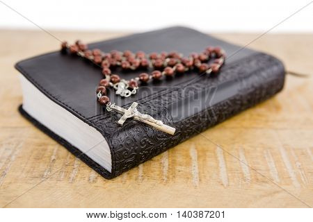 Close-up of bible and rosary beads on table