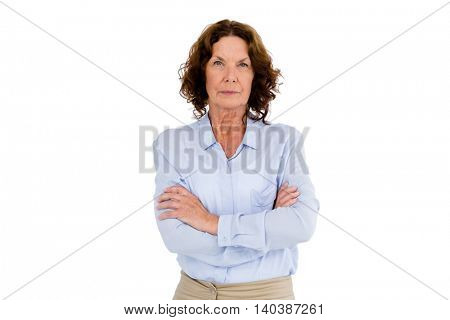 Serious mature woman with arms crossed while standing against white background