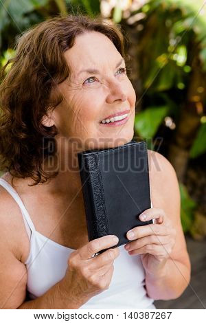 Smiling mature woman holding bible while looking away