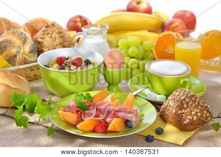 Laid breakfast table with melon and ham against a white background