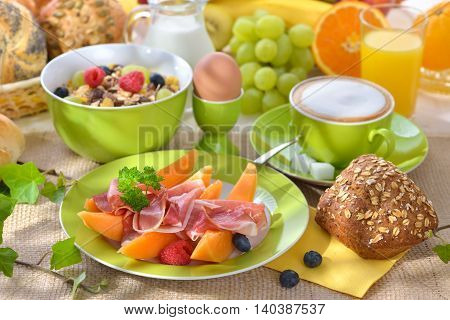 Laid breakfast table with honeydew melon, ham and a lot of fruits