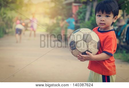 poor Asian boy playing an old foot ball in a village