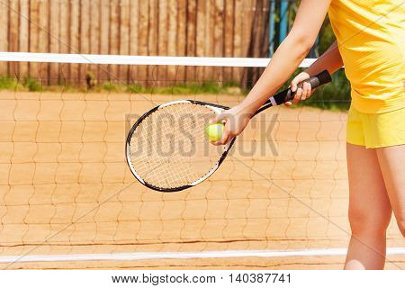 Picture of female player with tennis ball and racket preparing to serve on the clay court