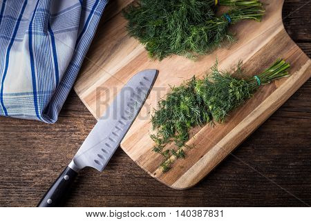 Sliced Twig Of Dill On A Wooden Board With Kknife