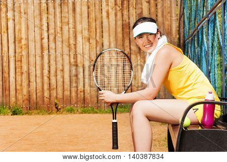 Side view of smiling teenage girl, tennis player, sitting on the bench after the game on the clay court