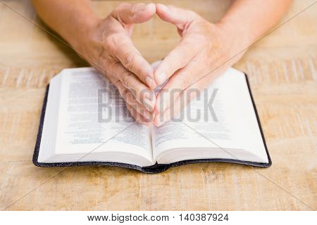 Cropped image of person with bible at table