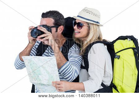 Man photographing while standing by woman with luggage against white backgroud