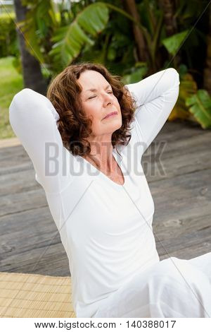 Mature woman with hands behind head while doing yoga