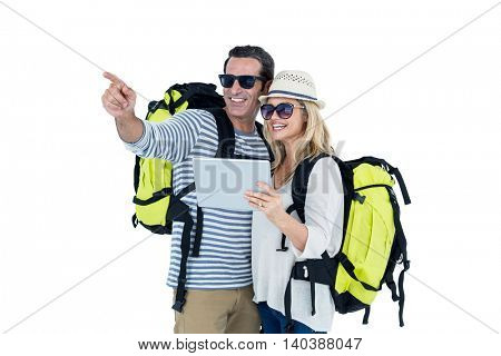 Cheerful couple with luggage against white background