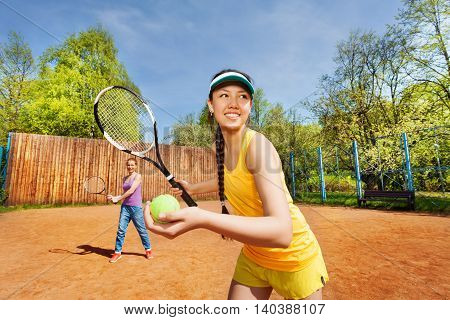 Female double tennis partners preparing to serve outdoors in summertime