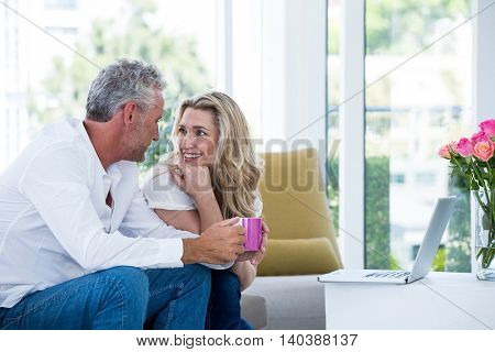 Happy mature couple with coffee mug and laptop while sitting at home