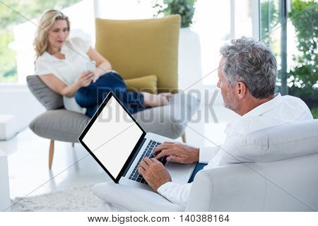 Mature man using laptop by woman sitting at home