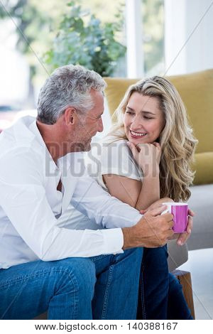 Smiling mature couple with coffee mug while sitting at home