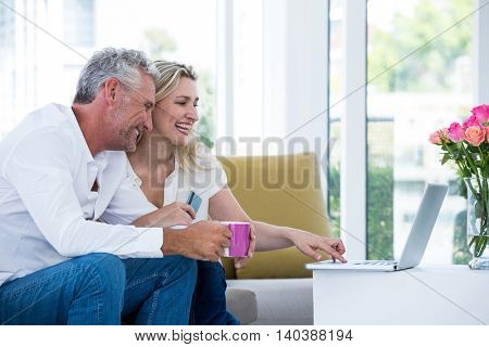 Happy couple using laptop while sitting at home