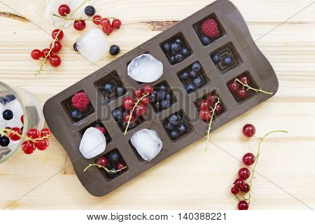 Brown ice cube tray with fresh wild berries on a wooden table: redcurrants blueberries and raspberries.