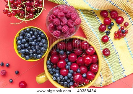 Summer fresh berries: blueberries raspberries cherries and redcurrent in bowls. Top view on a red and yellow background.