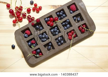 Diffrent types of berries in an ice cube tray with natural wooden background.