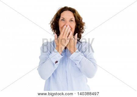 Portrait of smiling woman with hands covering mouth against white background