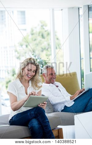 Happy mature couple using technology while sitting at home