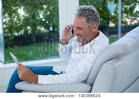Smiling man talking on phone while holding tablet at home