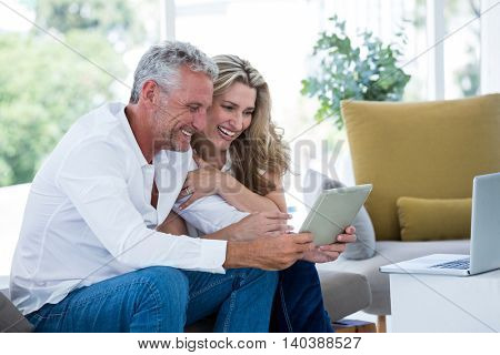 Smart mature couple using digital tablet while sitting at home